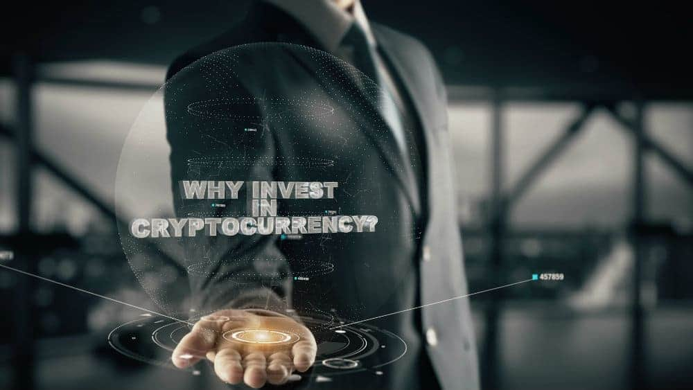 Businessman with his palm open containing a hologram saying 'Why Invest In Cryptocurrency?'