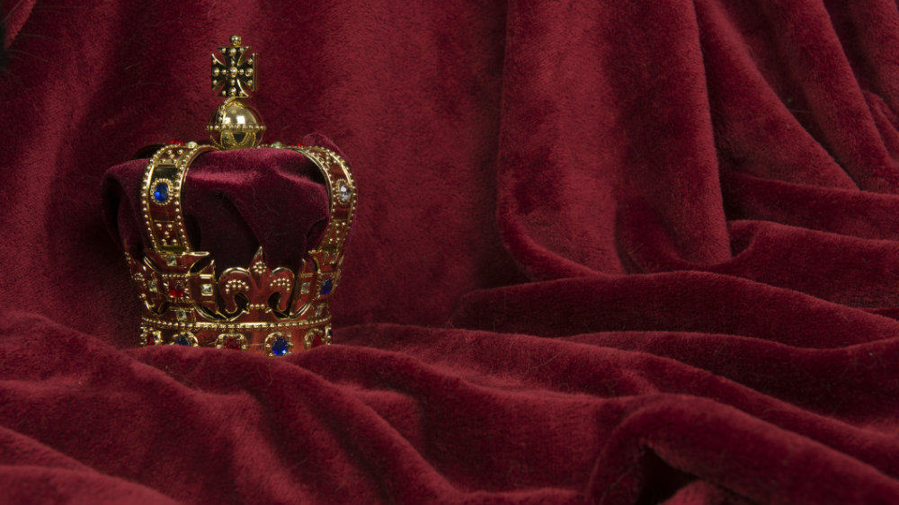 Golden crown on a red velvet background