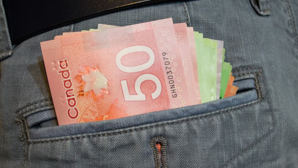 Various Canadian dollars in gray pants pocket